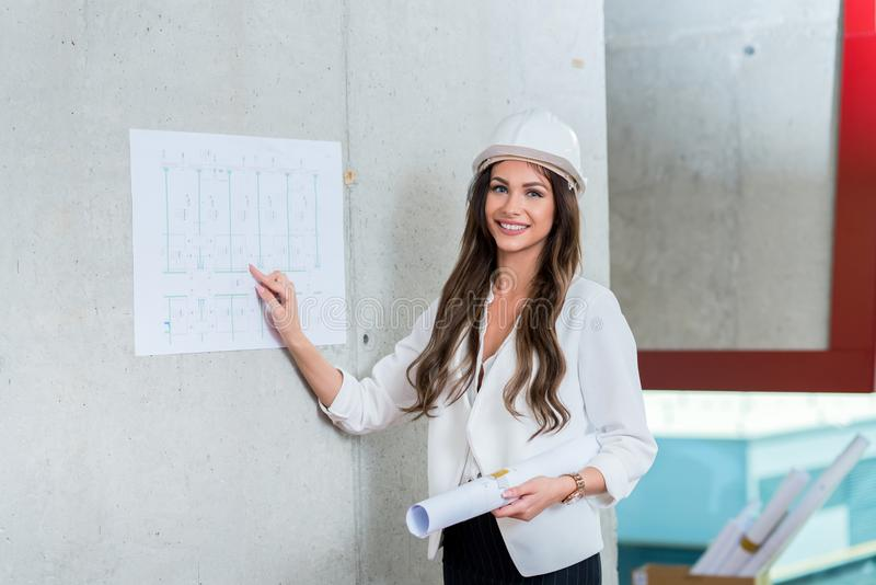 Business woman presenting architect blueprint. Making presentation during business meeting in office. stock image