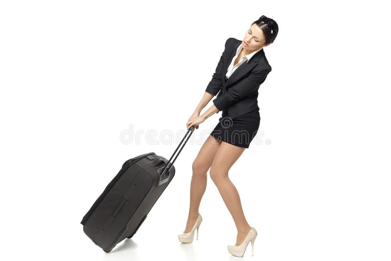 Business woman pulling her heavy suitcase royalty free stock photos