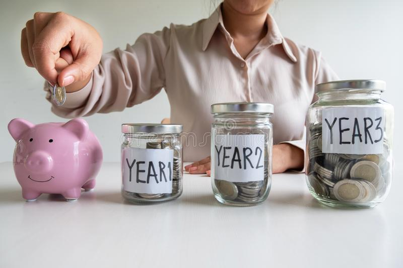 Business woman putting coin into pink piggy bank with 3 years planing account , step up growing business to success and saving for stock image