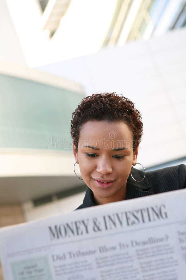 Business Woman Reading. A pretty african american business woman reading the newspaper royalty free stock images