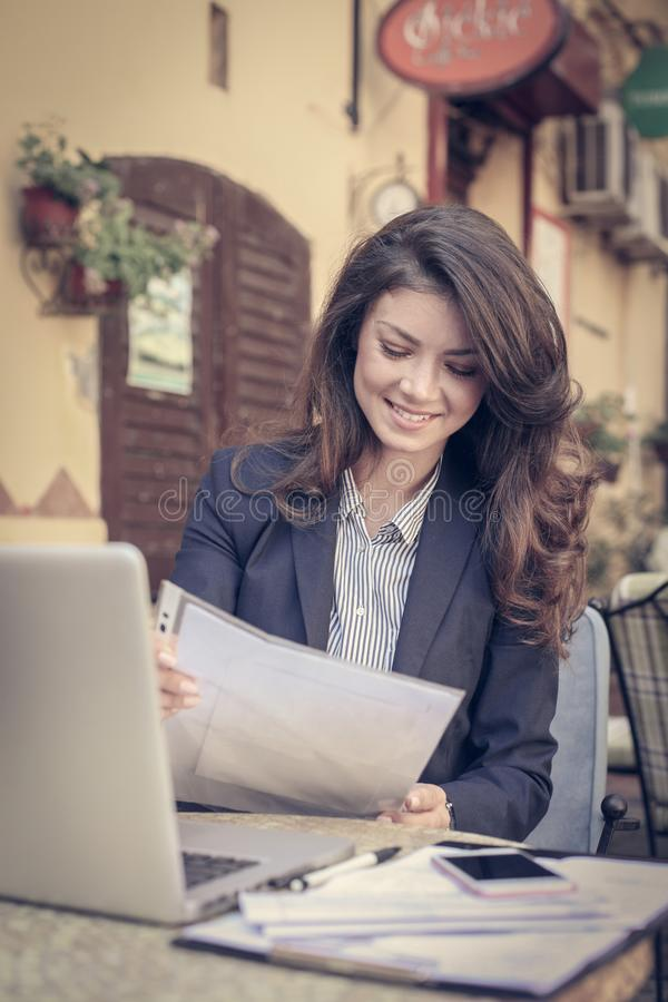 Business woman reading a documents, at cafe. royalty free stock photography