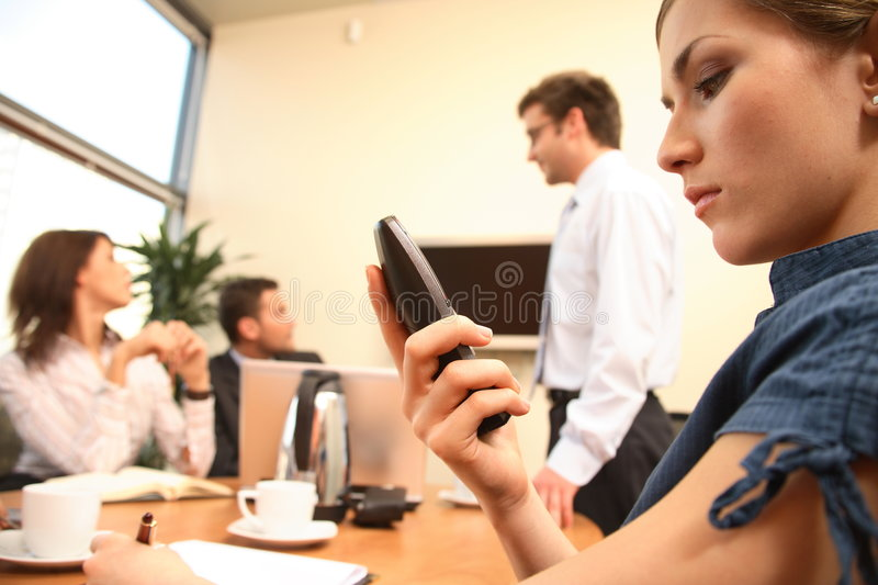 business woman reading message on mobile phone. presentation in background. stock image