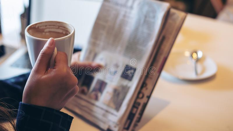 A business woman reading newspaper and drinking coffee stock images