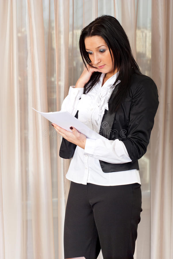 Business Woman Reading Papers In Office Royalty Free Stock Image