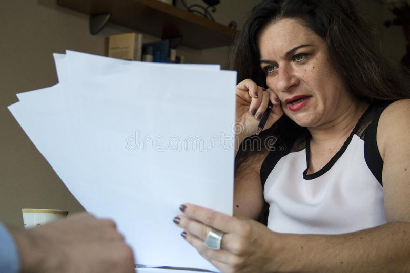 Business woman reading some reports at home office meeting. Business woman reading some reports at home office formal meeting royalty free stock image