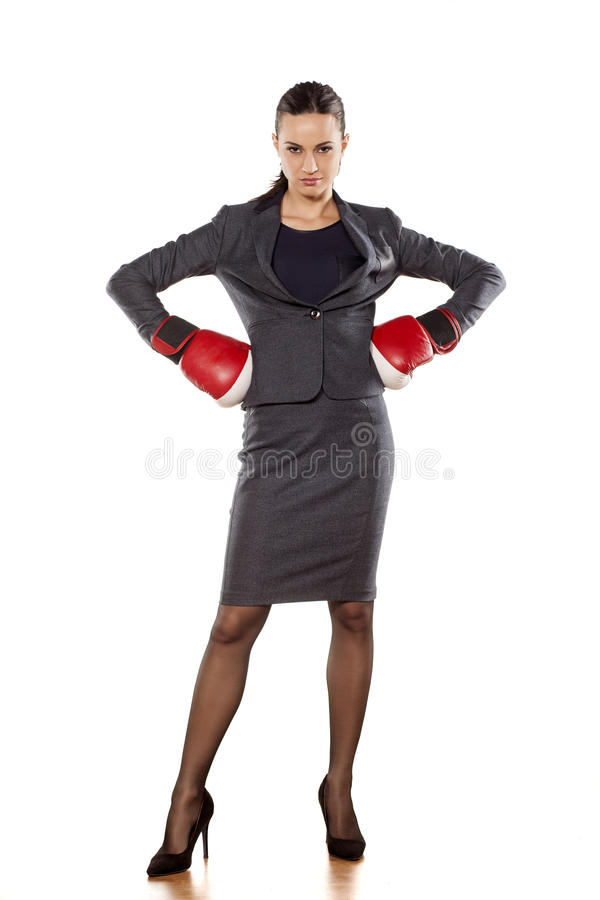 Business woman ready to fight. Angry business woman with boxing gloves on white background royalty free stock photography