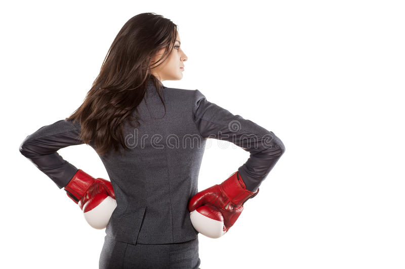 Business woman ready to fight. Back view of a business woman with boxing gloves on white background royalty free stock photo