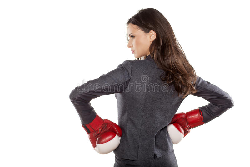 Business woman ready to fight. Back view of a business woman with boxing gloves on white background stock image