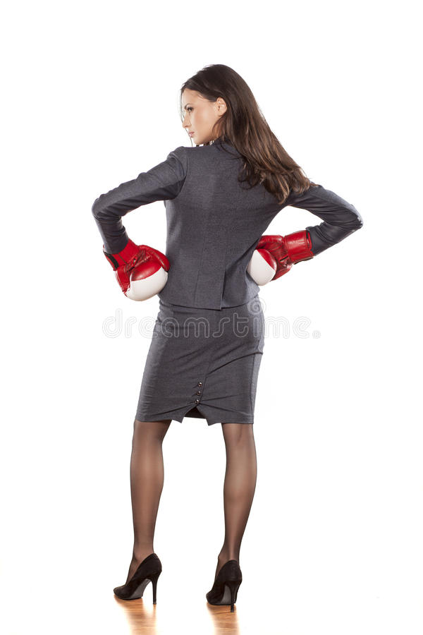 Business woman ready to fight. Back view of a business woman with boxing gloves on white background stock photography