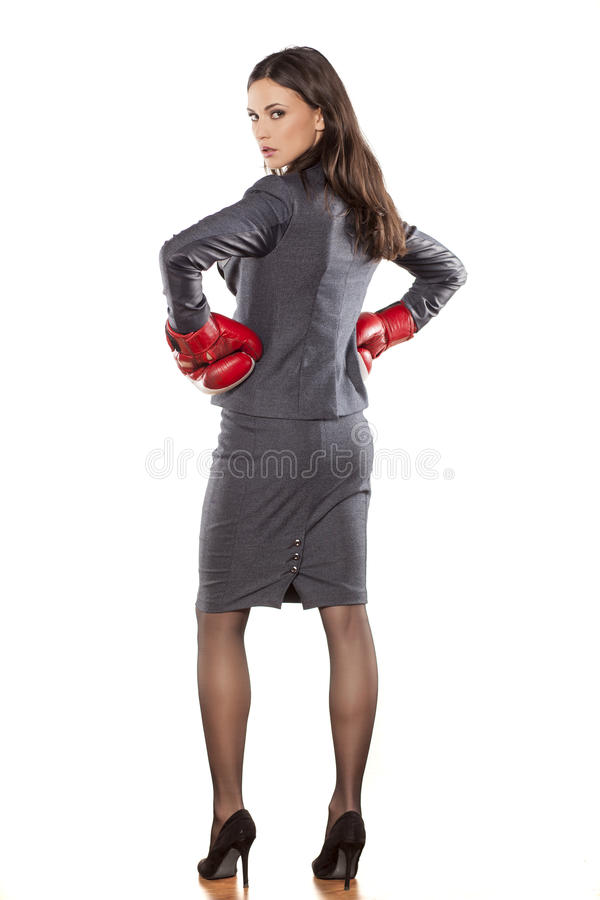 Business woman ready to fight. Back view of a business woman with boxing gloves on white background stock photo