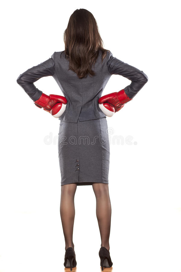 Business woman ready to fight. Back view of a business woman with boxing gloves on white background stock images