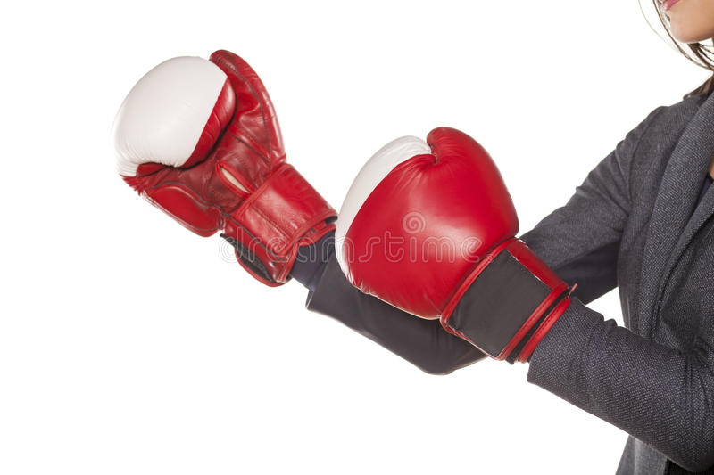 Business woman ready to fight. Hands of a business woman, attacking with boxing gloves stock image