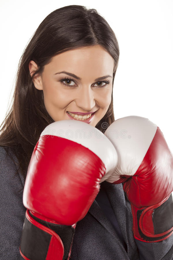 Business woman ready to fight. Happy business woman with boxing gloves on white background royalty free stock photo
