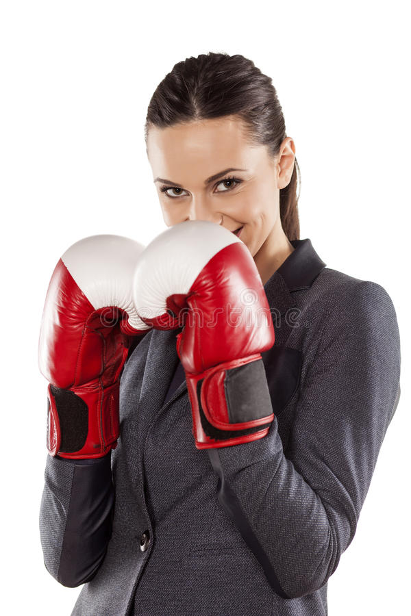 Business woman ready to fight. Happy business woman with boxing gloves on white background royalty free stock photography