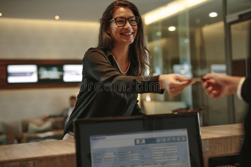 Business woman receiving key card for hotel room stock image