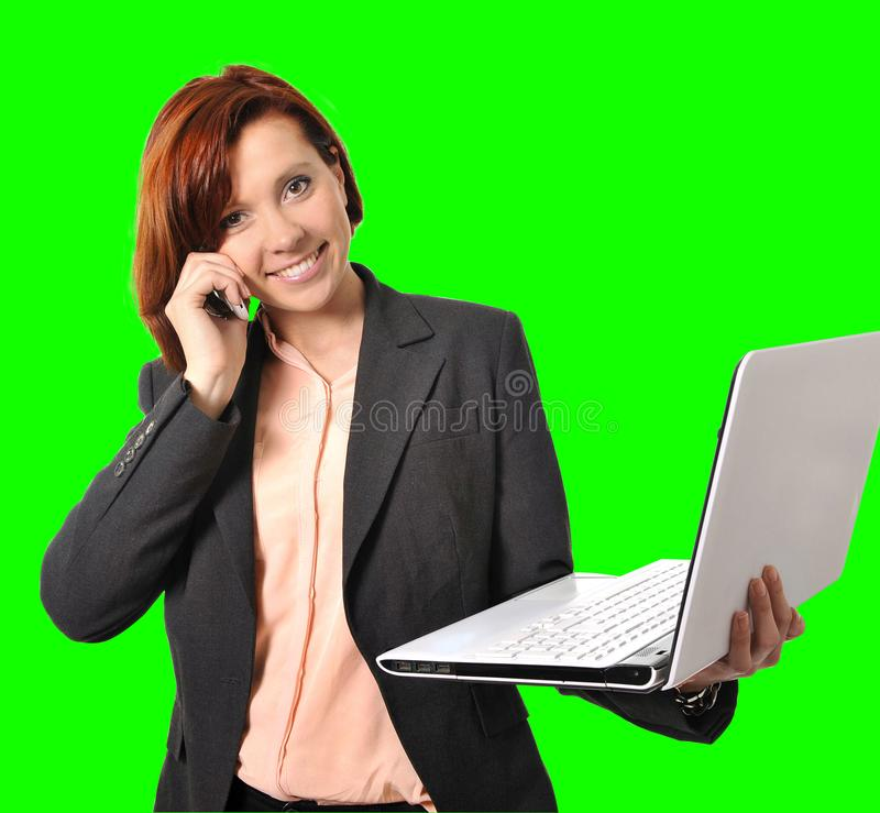 Business woman with red hair talking on the mobile cell phone holding laptop in hand isolated on green screen croma. Happy business woman with red hair talking stock image