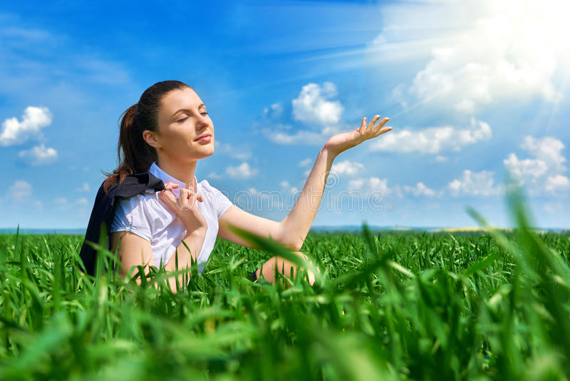 Business woman relaxing in green grass field outdoor under sun. Beautiful young girl dressed in suit resting, spring landscape, br. Ight sunny day royalty free stock photos