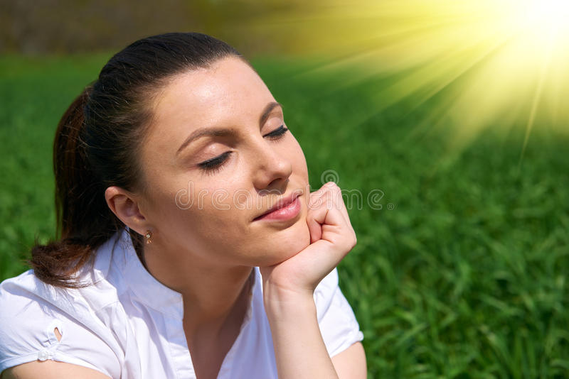 Business woman relaxing in green grass field outdoor under sun. Beautiful young girl dressed in suit resting, spring landscape, br. Ight sunny day stock photo