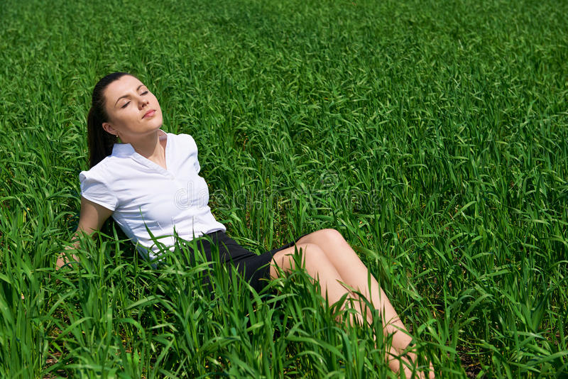 Business woman relaxing in green grass field outdoor under sun. Beautiful young girl dressed in suit resting, spring landscape, br. Ight sunny day royalty free stock photo