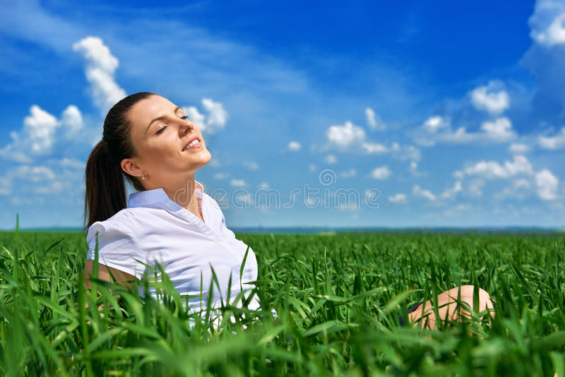 Business woman relaxing in green grass field outdoor under sun. Beautiful young girl dressed in suit resting, spring landscape, br. Ight sunny day stock photos