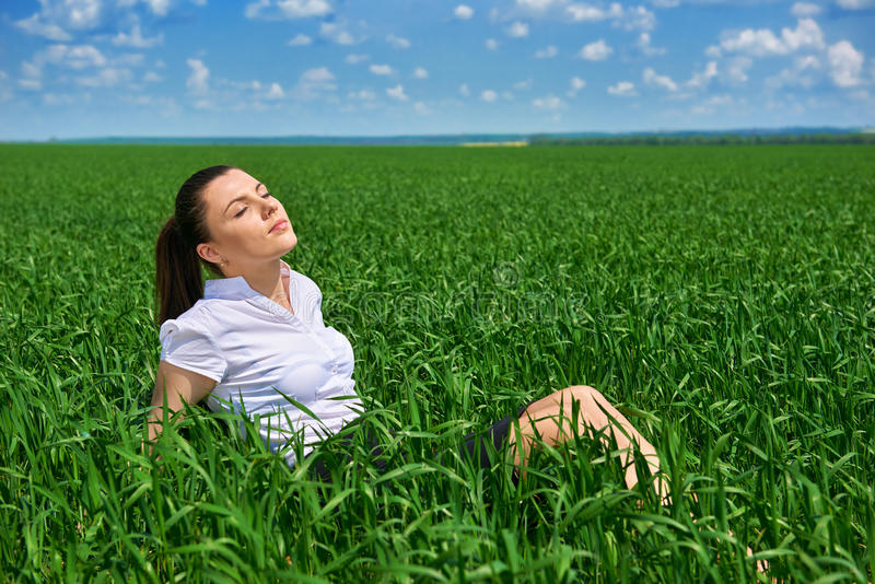 Business woman relaxing in green grass field outdoor under sun. Beautiful young girl dressed in suit resting, spring landscape, br. Ight sunny day stock images