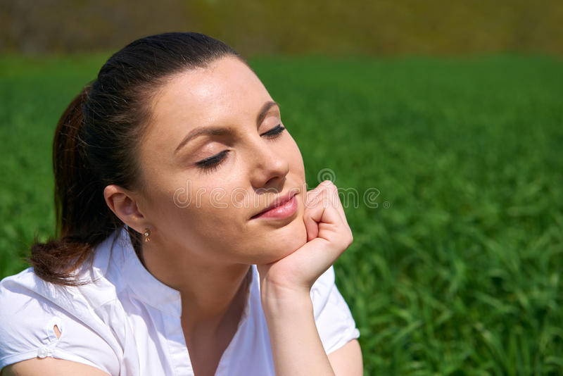 Business woman relaxing in green grass field outdoor under sun. Beautiful young girl dressed in suit resting, spring landscape, br. Ight sunny day stock photography