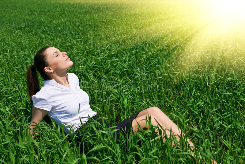 Business woman relaxing in green grass field outdoor under sun. Beautiful young girl dressed in suit resting, spring landscape, br. Ight sunny day stock image