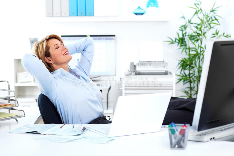 Business woman. Relaxing mature business woman. In a modern office stock photography