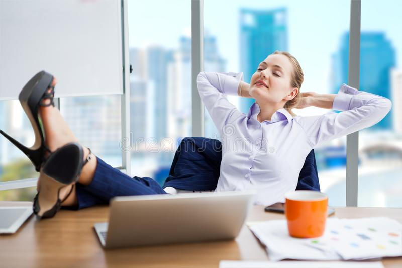 business woman relaxing or sleeping with her feet on the desk in royalty free stock photo