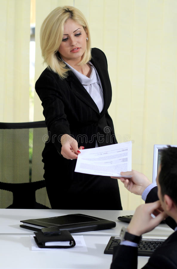 Business woman resigns her job. Business woman handing a letter of resignation to her male boss stock photo