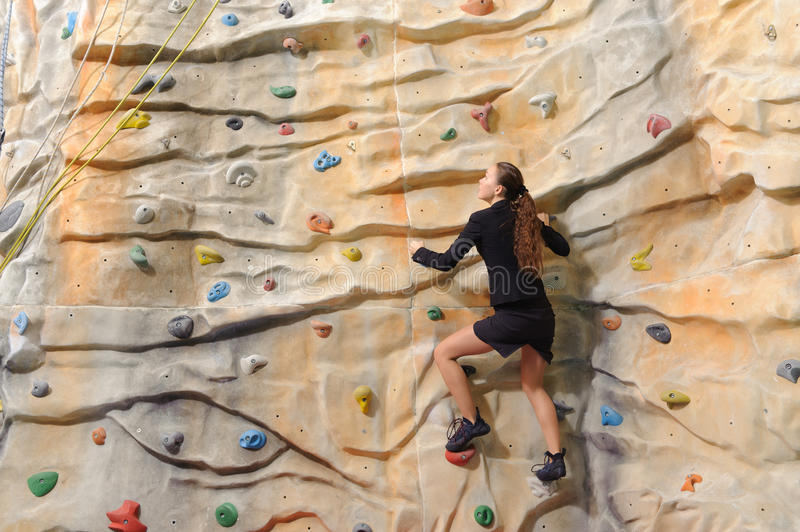 Business woman on rock wall. Active young business woman on rock wall in sport center royalty free stock image