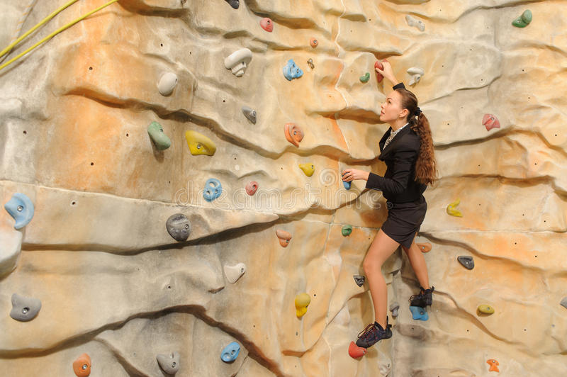 Business woman on rock wall. Active young business woman on rock wall in sport center royalty free stock images