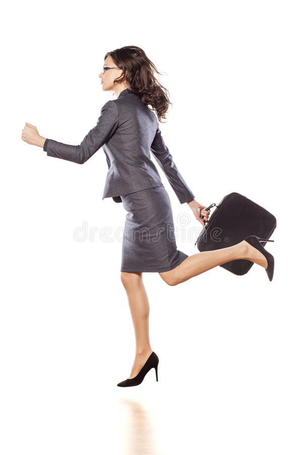 Business woman running. Young exited business woman in jacket and skirt holding a briefcase and running stock photos