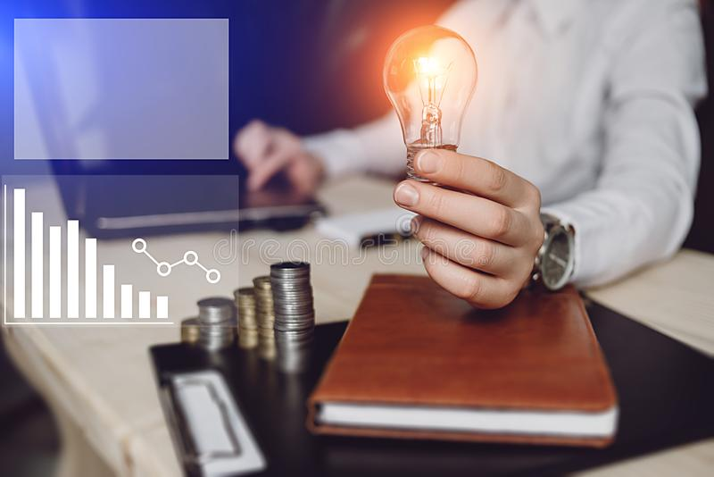 Business woman`s hand holding light bulb with using notebook and notebook and money stack. Idea saving energy and accounting. Finance. digital marketing media stock images