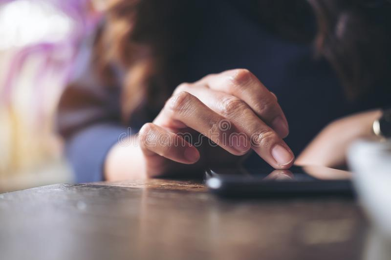 A business woman`s hand touching and sliding finger on a black smart phone on wooden table royalty free stock image