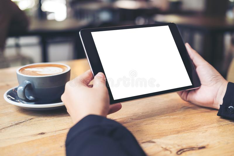 Business woman`s hands holding black tablet with white blank screen and coffee cup on wooden table in cafe royalty free stock image