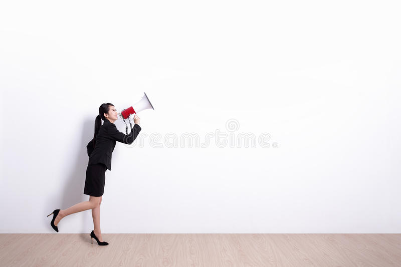 Business woman screaming. Business woman talking in megaphone with white wall background, great for your design or text, asian royalty free stock images