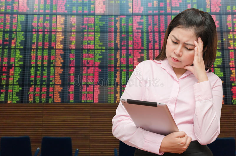 Business woman see tablet screen for loss value and feel pain strain with stock board royalty free stock photo