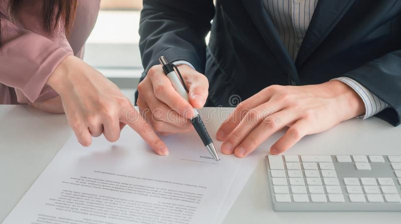 Business woman send document to businessman for signature on his desk stock images