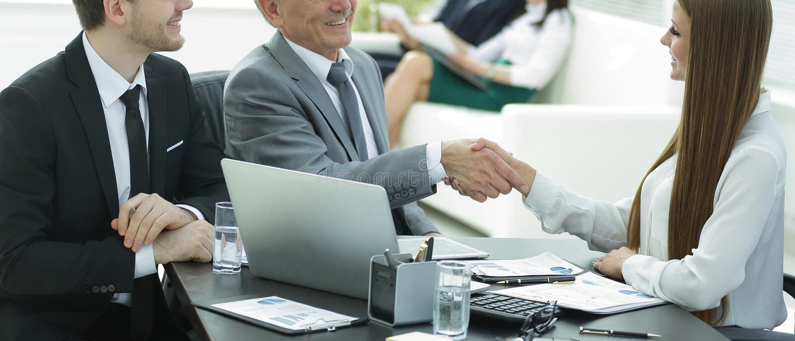 Business woman shaking hands with an adult business partner. royalty free stock image