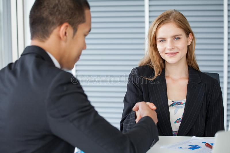 business woman shaking hands with businessman in office . girl looking at camera stock photo