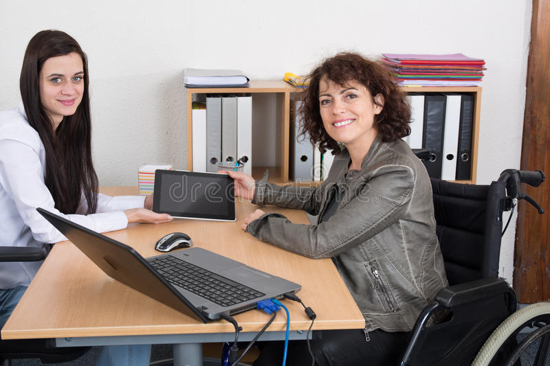 Business woman shaking hands with disabled colleague at desk stock image