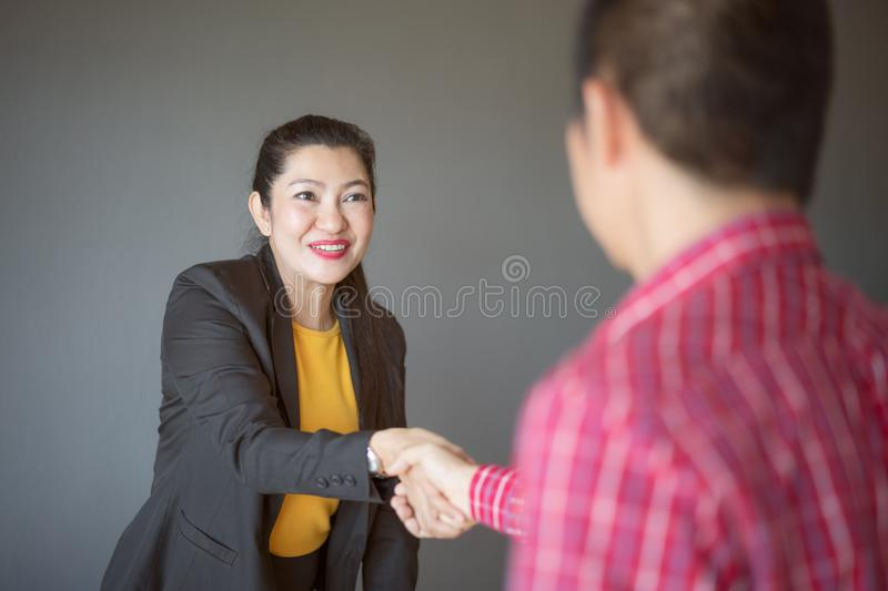 Business woman shaking hands with an engineer for a successful project stock photography