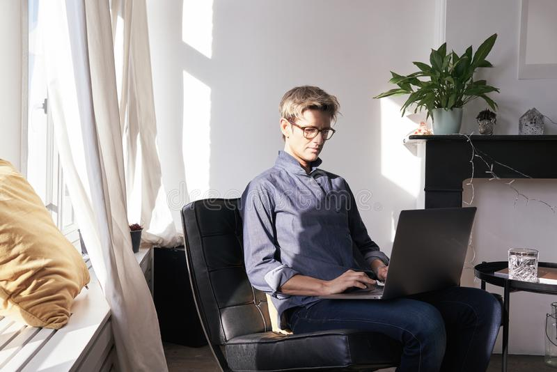 Business woman with short hair and glasses working on laptop at modern apartment, opened window, sunny daylight. Concept of young royalty free stock photos