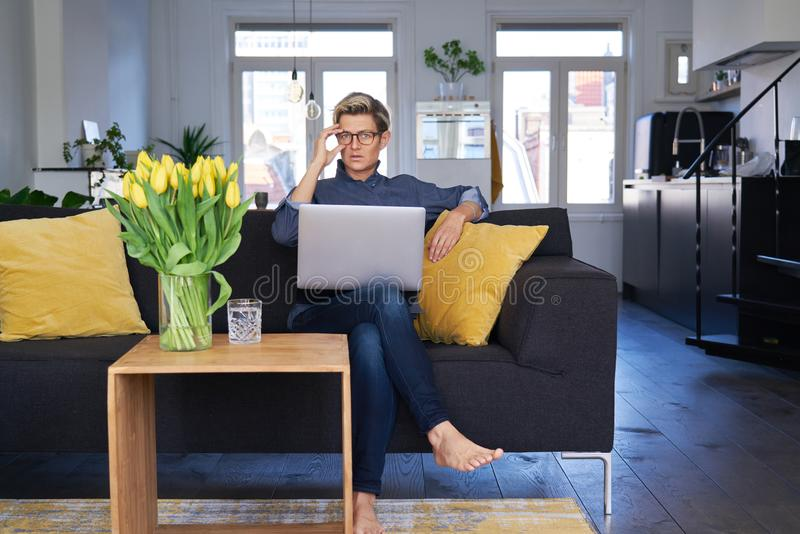 Business woman with short hair and glasses working on laptop at modern apartment, sunny daylight. Concept of young entrepreneur royalty free stock images