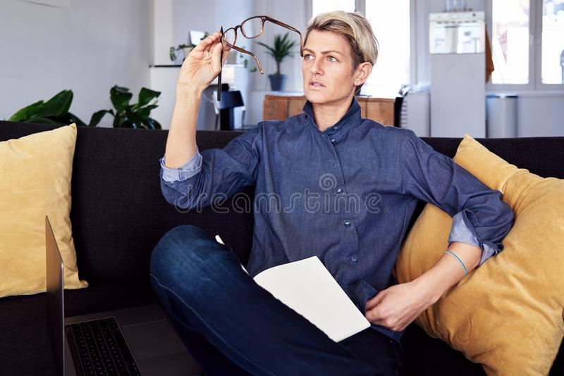 Business woman with short hair looks into glasses, makign notes, using laptop at modern apartment. Concept of young entrepreneur royalty free stock image