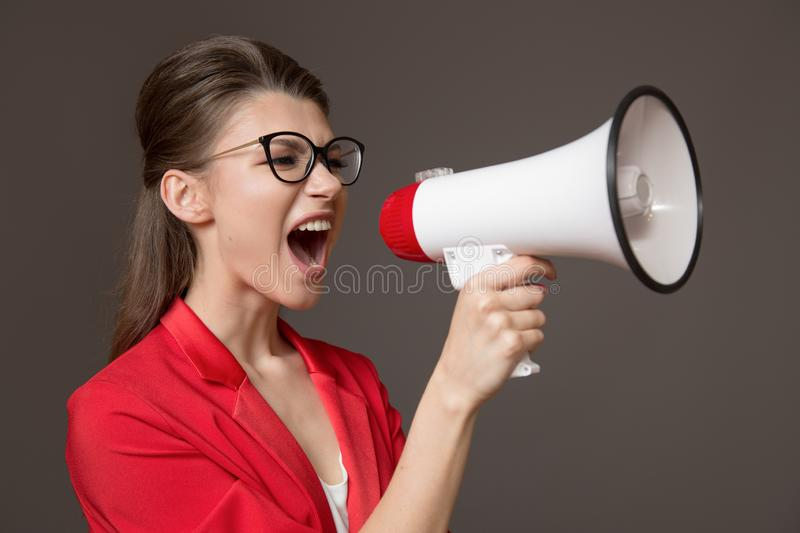 Business woman shouting at a megaphone. Young pretty girl in glasses and a red jacket royalty free stock photo