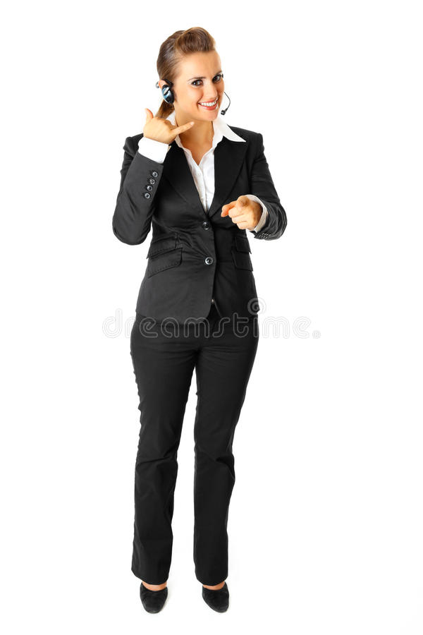 Business woman showing contact me gesture. Smiling modern business woman with headset showing contact me gesture isolated on white royalty free stock images