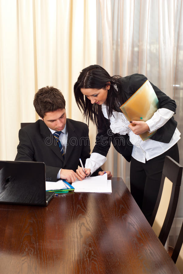 Business woman signing an agreement. For other business man partner in a meeting room royalty free stock image