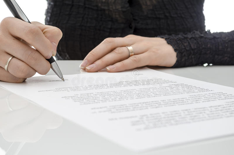 Business woman signing a contract above signature line stock photo